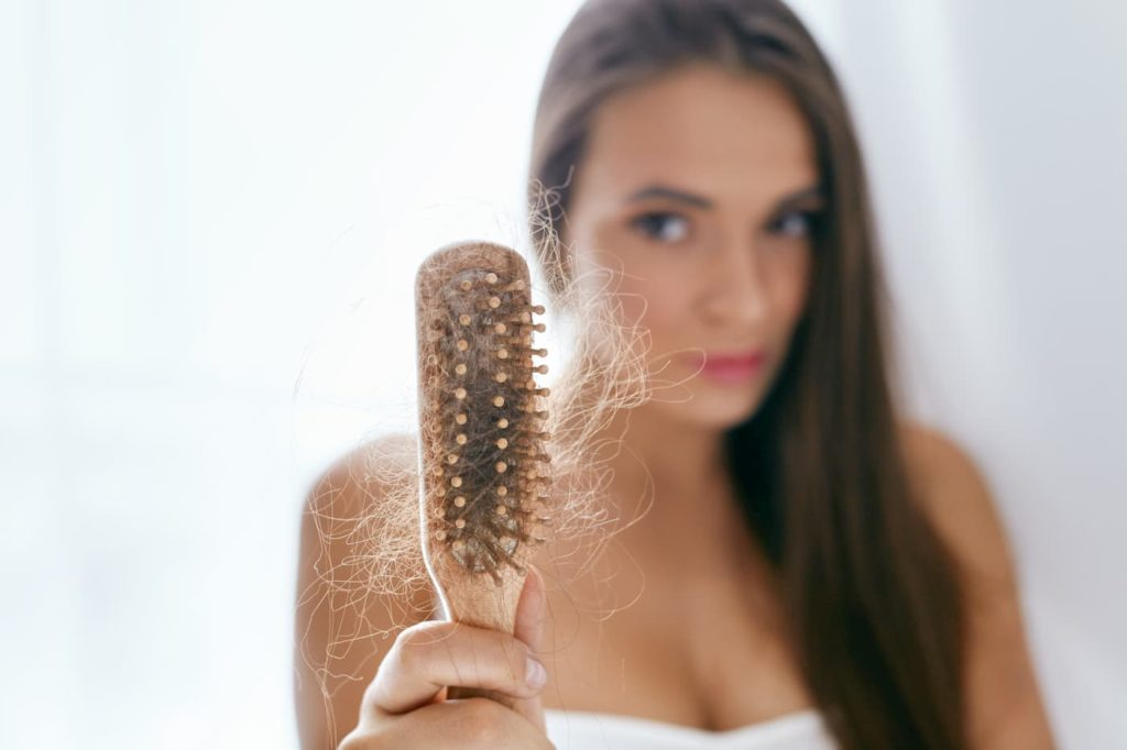 Woman holding a brush with lots of hair in it - What Are Some Carnivore Diet Hair Loss Causes
