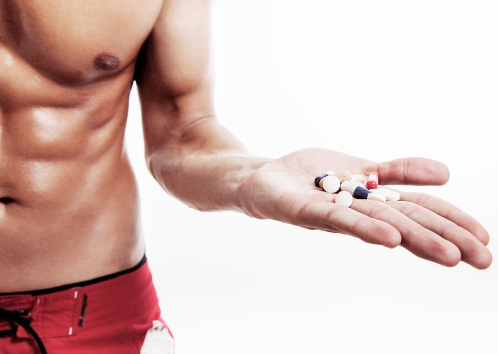 Man holding out supplements in pill form - What Supplements Should I Take on The Carnivore Diet